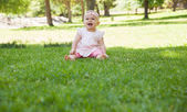 Cheerful cute baby sitting on grass at park — Stock Photo