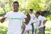 Volunteer pointing at tshirt in park — Stock Photo