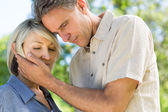 Man comforting woman in park — Stock Photo