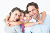 Smiling young family looking at camera together — Stock Photo