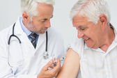 Doctor injecting senior male patient — Stock Photo