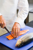 Closeup mid section of a chef cutting fish — Stock Photo