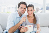Couple watching movie on the sofa with bowl of popcorn — Stock Photo