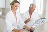 Couple shopping online and reading newspaper in bathrobes — Stock Photo