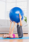 Blonde holding exercise ball between legs — Photo