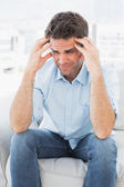 Grimacing man sitting on the couch with a headache — Stock Photo