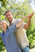 Couple with arms outstretched in park — Stockfoto