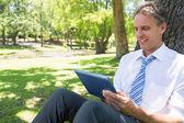 Podnikatel pomocí digitálních tabletu v parku — Stock fotografie