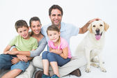 Cute family with pet labrador posing and smiling at camera together — Stock Photo