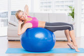 Blonde doing sit ups on exercise ball — Stock Photo