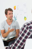 Young man talking to colleagues at a meeting — Stock Photo