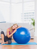 Fit blonde sitting beside exercise ball — Stock Photo