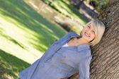 Woman leaning on tree trunk in parkland — Stock Photo