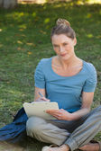 Relaxed young woman writing on clipboard at park — Stock Photo
