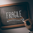 Hand writing Fragile on chalkboard — Stock Photo #42972527