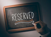 Hand writing Reserved on chalkboard — Stock Photo