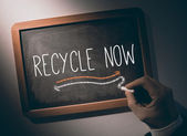 Hand writing Recycle now on chalkboard — Stock Photo