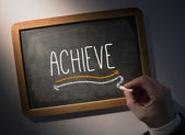 Hand writing Achieve on chalkboard — Stock Photo