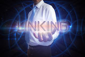 Businessman presenting the word linking — Stock Photo