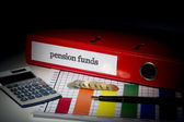Pension funds on red business binder  — Stock Photo