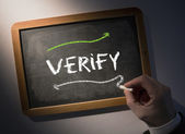 Hand writing Verify on chalkboard — Stock Photo