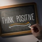Hand writing Think positive on chalkboard — Stock Photo