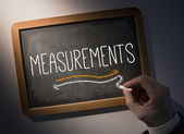 Hand writing Measurements on chalkboard — Stock Photo