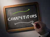 Hand writing Competitors on chalkboard — Stock Photo