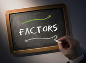 Hand writing Factors on chalkboard — Stock Photo