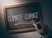 Hand writing Climate change on chalkboard — Stock Photo