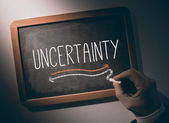 Hand writing Uncertainty on chalkboard — Stock Photo