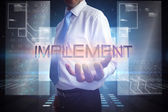 Businessman presenting the word implement — Stock Photo