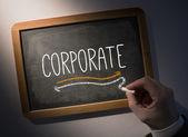Hand writing Corporate on chalkboard — Stockfoto