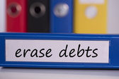 Erase debts on blue business binder — Stock Photo
