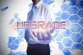 Businessman presenting the word upgrade — Stock Photo