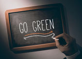 Hand writing go green on chalkboard — Stock Photo