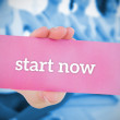 Woman holding pink card saying start now — Stock Photo #44884807