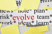 Evolve against sticky notes strewn over notepad — 图库照片