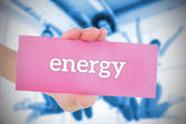 Woman holding pink card saying energy — Stock Photo