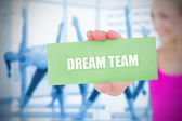 Fit blonde holding card saying dream team — Stock Photo