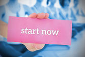 Woman holding pink card saying start now — Stock Photo