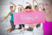 Woman holding pink card saying triumph — Stockfoto