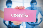 Woman holding pink card saying exercise — Stock Photo