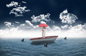 Businesswoman holding umbrella in a sailboat — Stock Photo