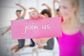 Woman holding pink card saying join us — Stockfoto