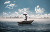 Businessman standing back to camera in a sailboat — Stock Photo
