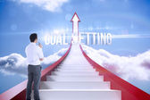 Goal setting against red steps arrow pointing up against sky — Stock Photo