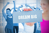 Fit blonde holding card saying dream big — Stock Photo