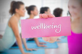 Woman holding pink card saying wellbeing — Stock Photo