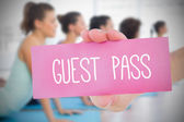 Woman holding pink card saying guest pass — Stock Photo